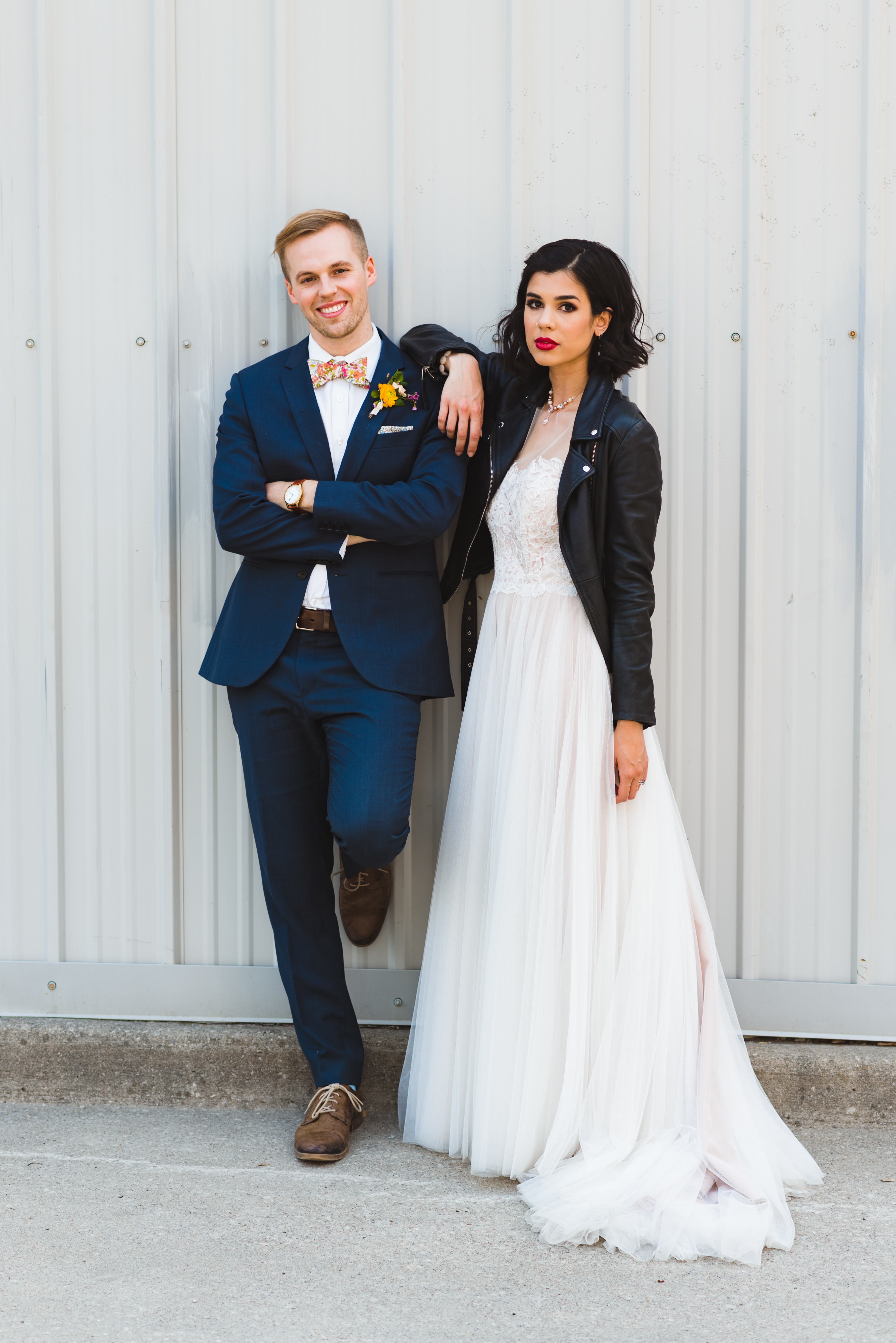 bride wearing black just married leather jacket over white wedding dress with one arm on grooms shoulder in front of white metal wall Toronto wedding photography