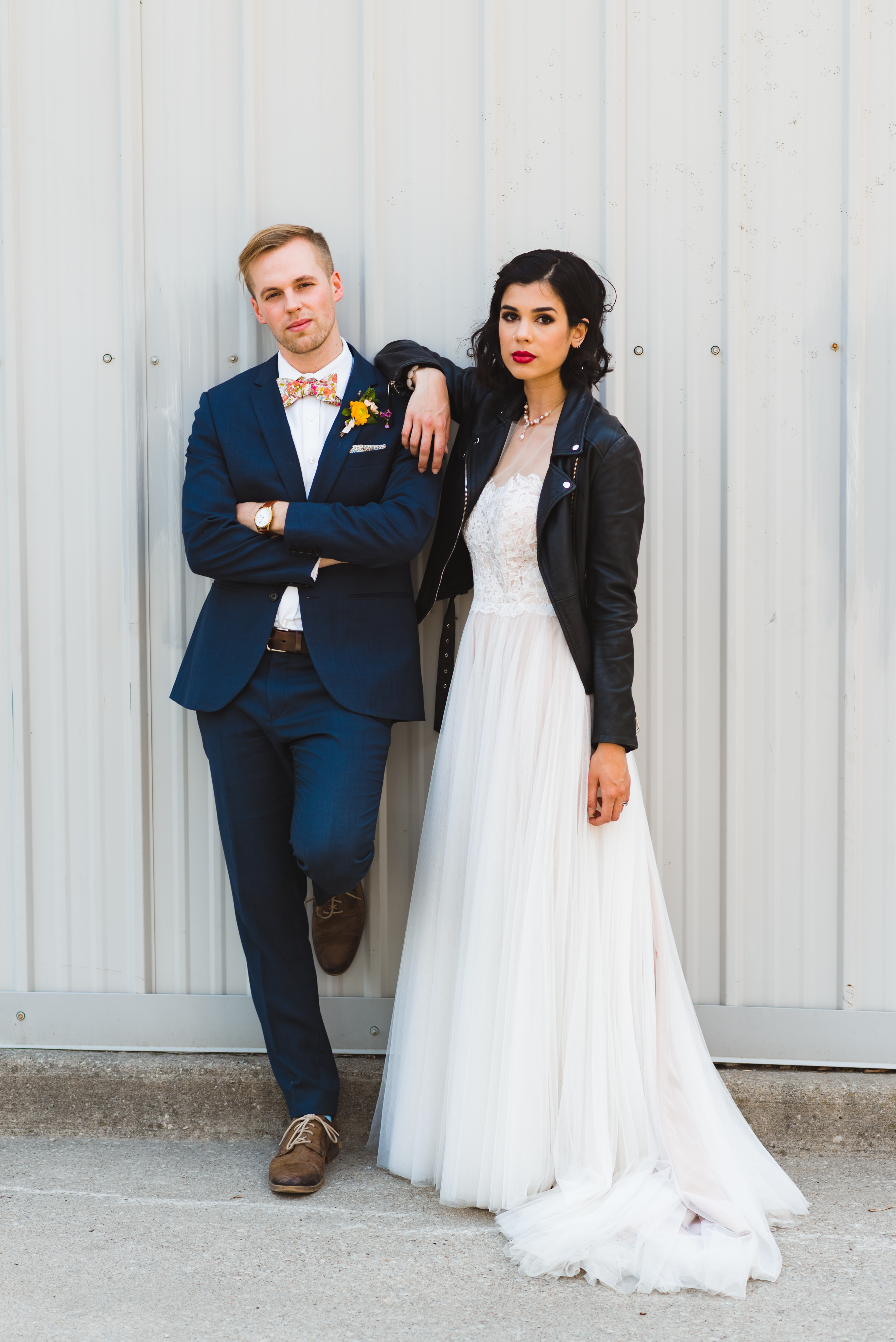 bride wearing just married leather jacket leaning against Jam Factory wall with groom wedding photography