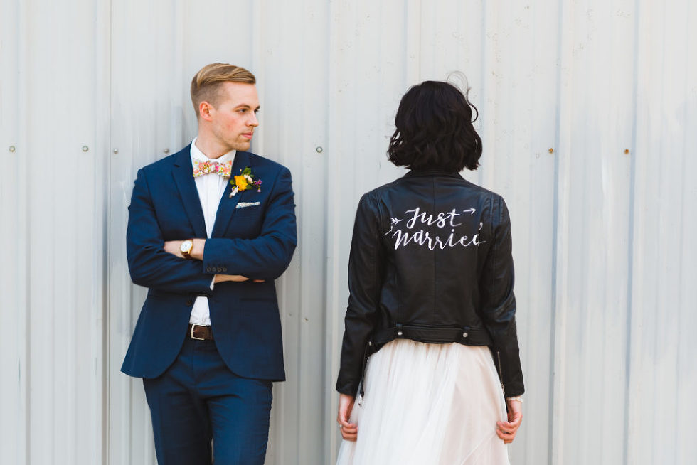 bride wearing black just married leather jacket over white wedding dress next to groom in front of white metal wall Toronto wedding photography