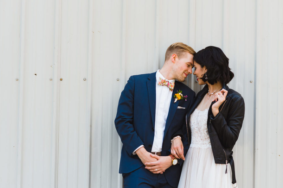 bride in black just married leather jacket and wedding dress in loving embrace with her groom Toronto wedding photography