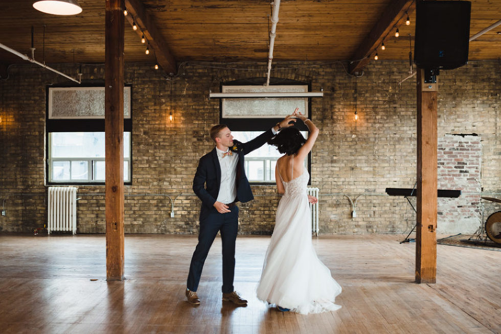 groom twirls his bride on dance floor inside Jam Factory Toronto wedding photography