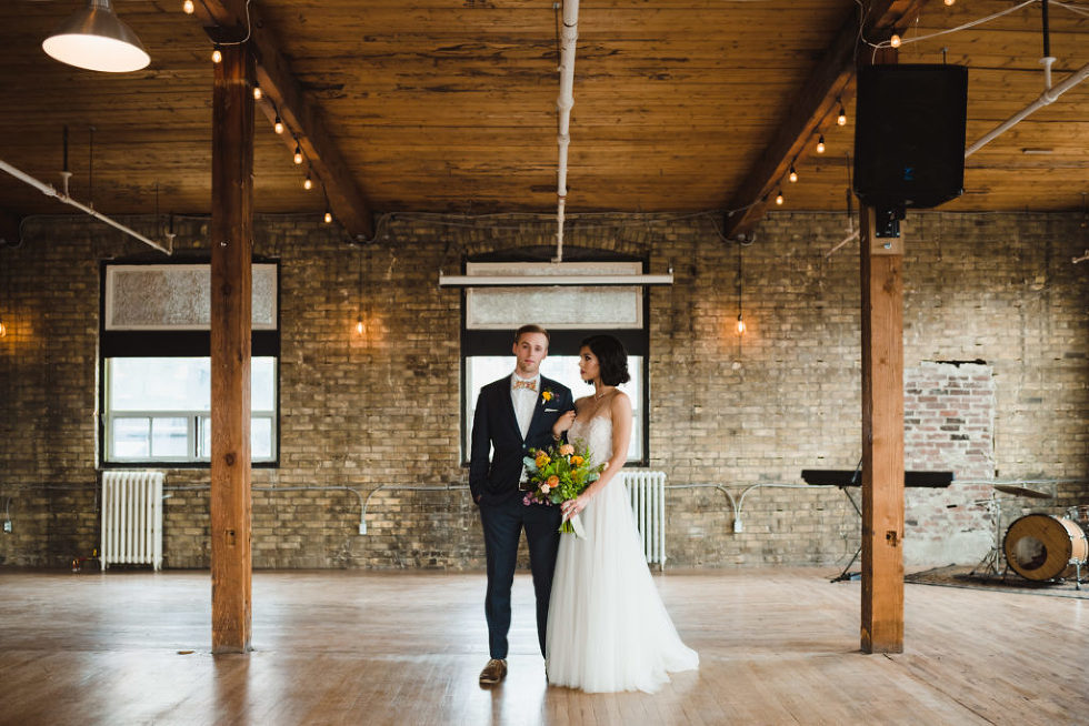bride holding floral bouquet next to her groom at Jam Factory Toronto wedding photography