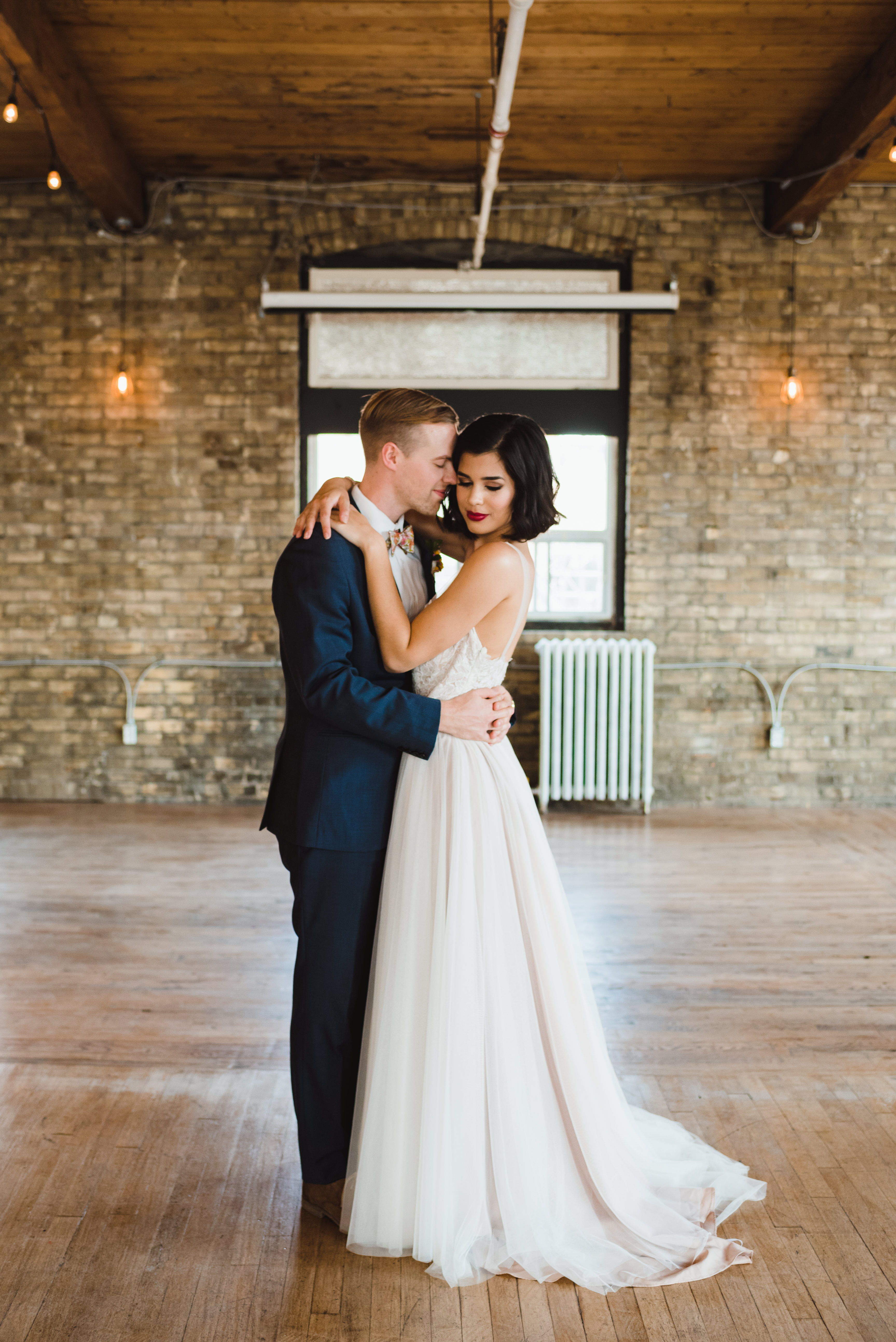 bride and groom loving embrace inside old brick building Toronto wedding photography