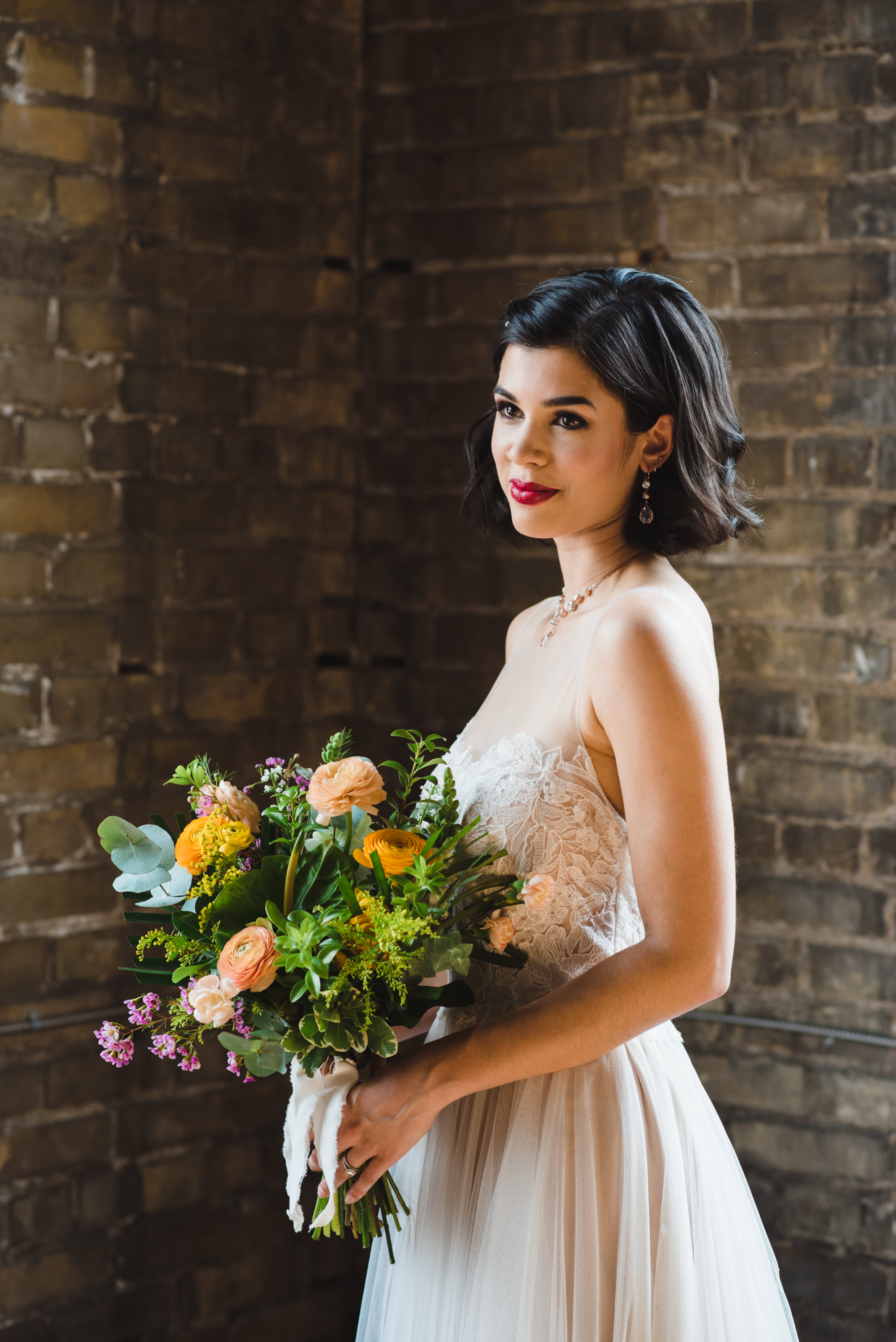 bride and her bouquet standing in front of old brick wall at the Jam Factory Toronto wedding photography