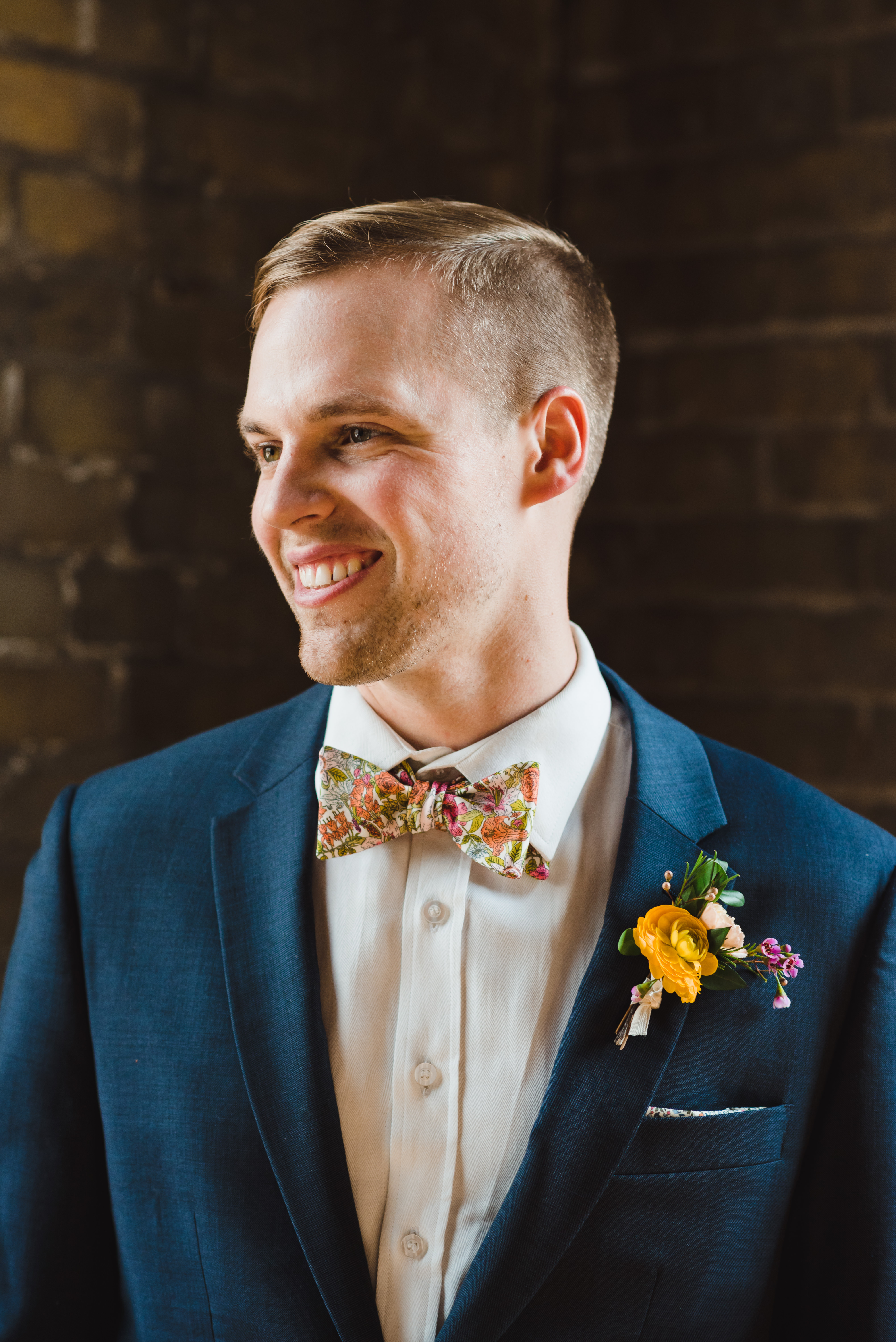 groom with floral bowtie and boutonniere smiling at the Jam Factory Toronto wedding photography