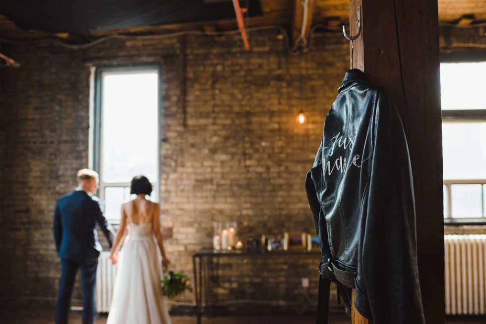 just married leather jacket hanging up on a wooden post with the bride and groom holding hands and facing brick wall and wedding decorations at the Jam Factory Toronto wedding photography