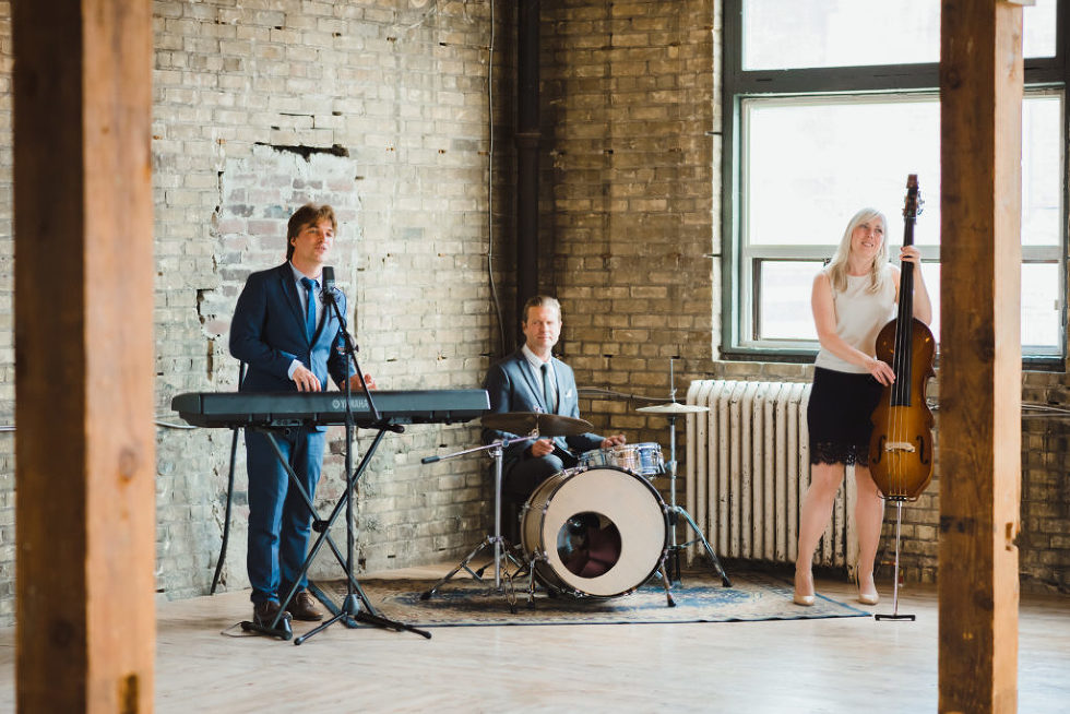 3 piece wedding band playing in the corner of the Jam Factory brick wall Toronto wedding photography