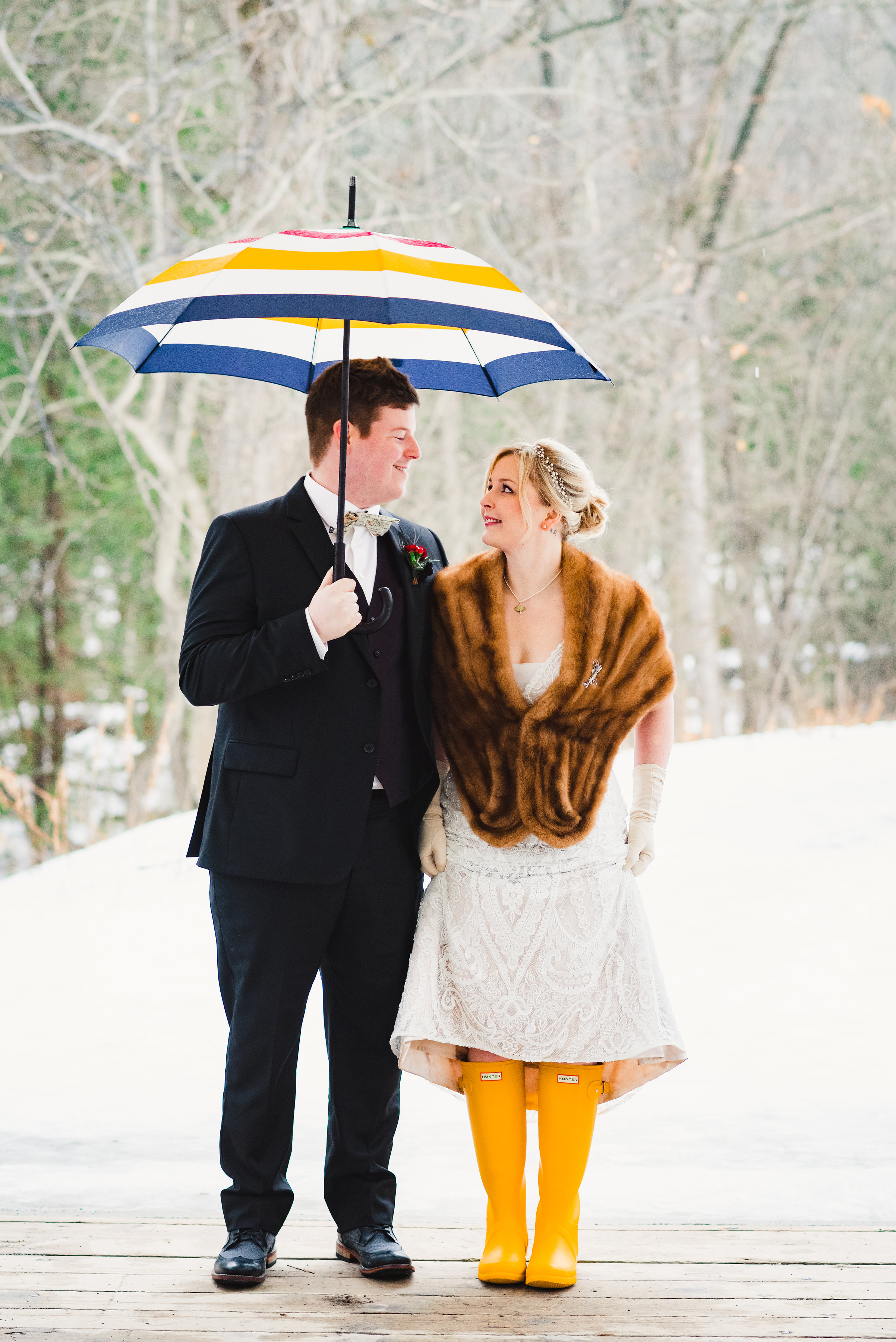 bride and groom stand underneath colourful umbrella in the snow looking into each other eyes Canadian Canoe Museum wedding