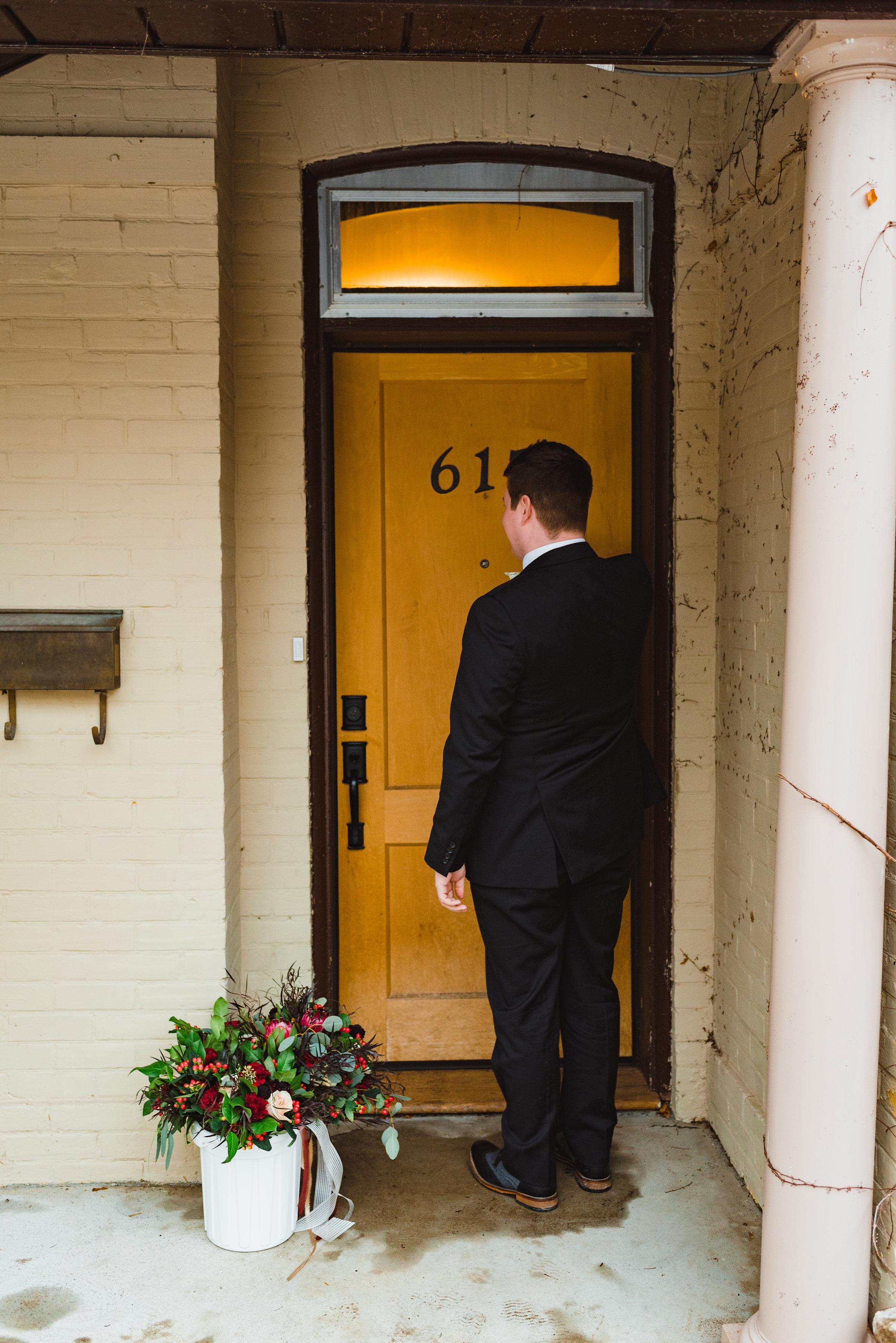 groom stands before a yellow door waiting for his bride Canadian Canoe Museum wedding