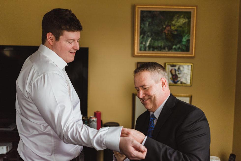 father of groom helping groom with his cufflinks Toronto wedding photographer