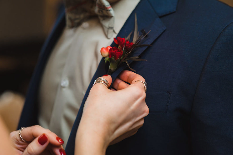 woman placing red boutonniere on grooms blue suit jacket Toronto wedding photographer Gillian Foster