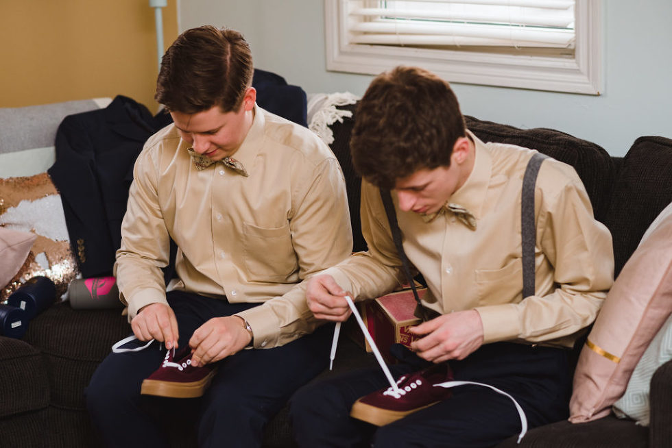 groomsmen sitting on a couch untying the laces of their shoes Toronto wedding photographer Gillian Foster