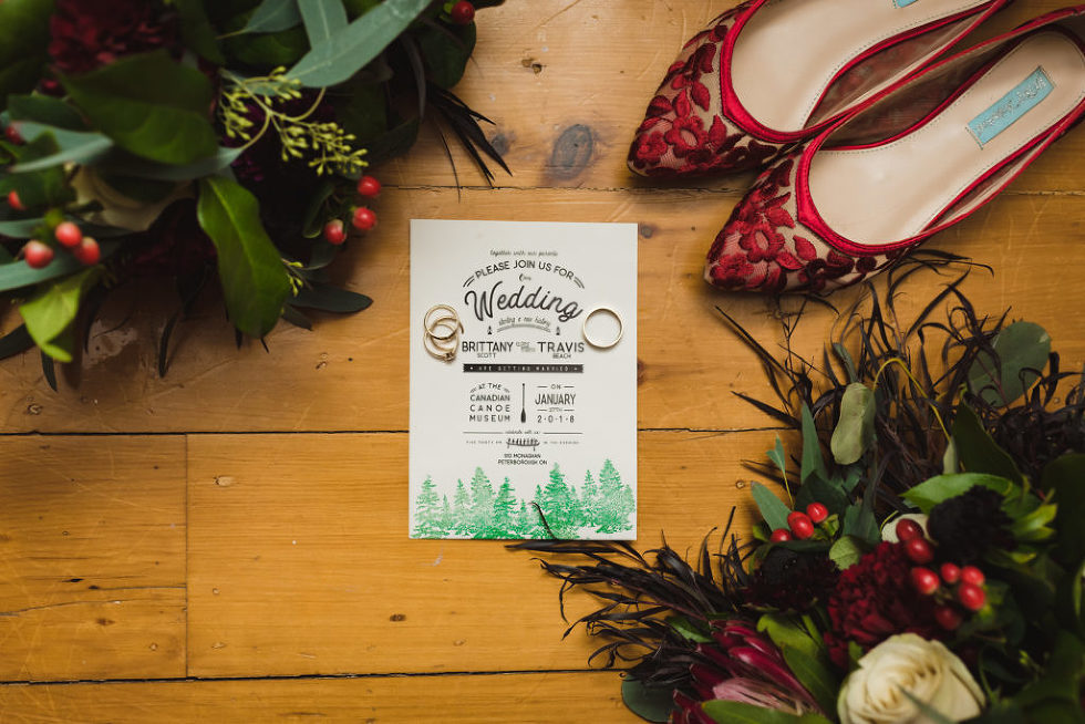 bouquets and shoes placed around wedding invitation and wedding rings Toronto wedding photographer