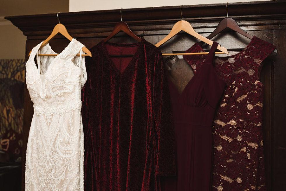 wedding dress hanging up next to maroon bridesmaids dresses Canadian Canoe Museum wedding Peterborough