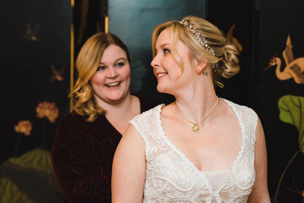 bridesmaid standing behind bride smiling Canadian Canoe Museum wedding Peterborough photographer
