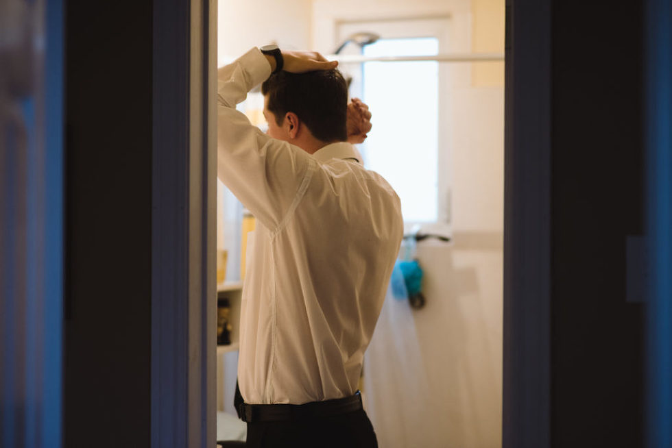 groom doing his hair in the bathroom Canadian Canoe Museum wedding Gillian Foster