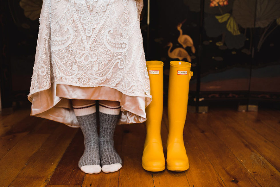 bride in her wedding dress and wool socks standing next to yellow rain boots Canadian Canoe Museum wedding