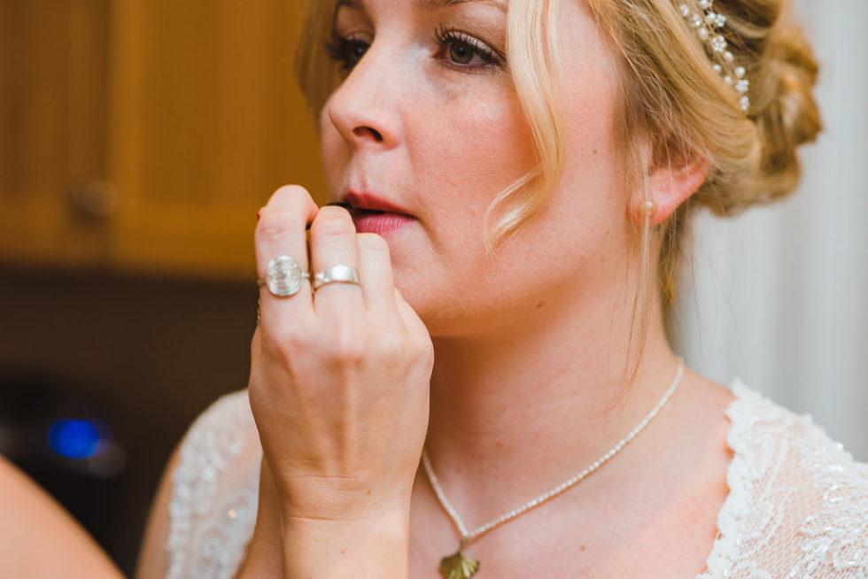 bride having her lipstick applied by her makeup artist Canadian Canoe Museum wedding