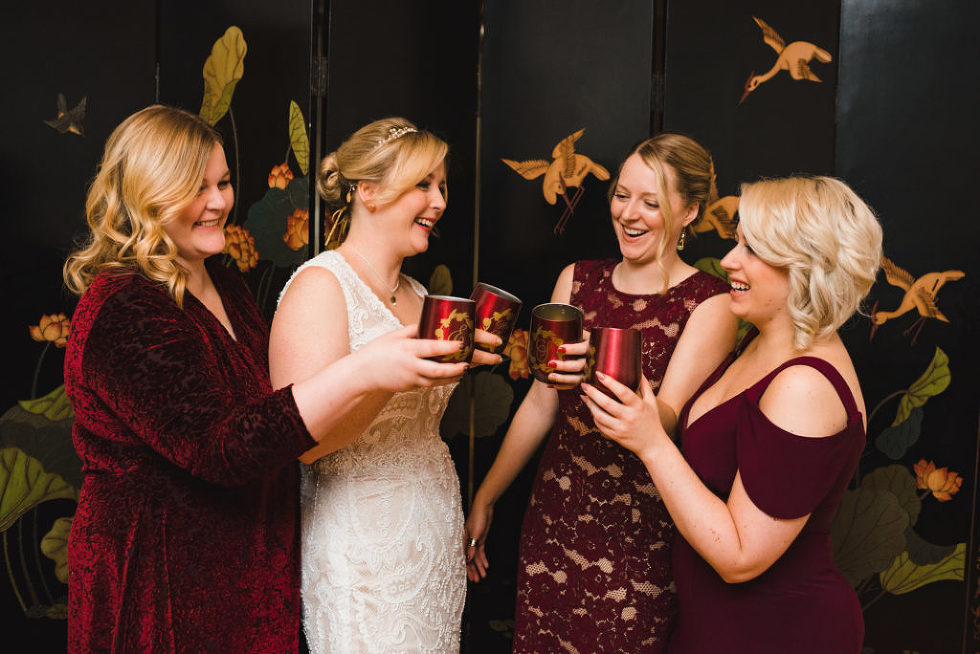bride and bridesmaids toasting with red cups before wedding ceremony Canadian Canoe Museum Peterborough