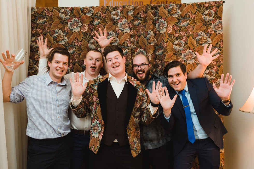 groom taking a picture with wedding guests with all their hands in the air Canadian Canoe Museum wedding photography