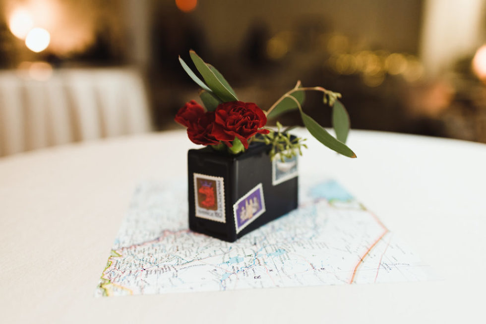 wedding reception centrepiece with red roses and map placed underneath it Canadian Canoe Museum