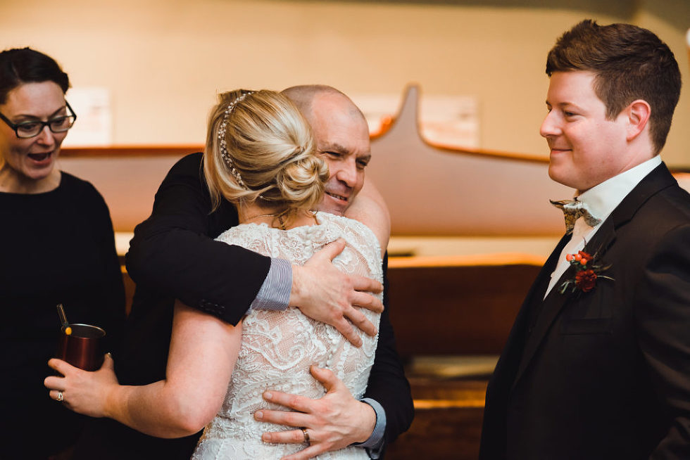bride being hugged during wedding reception at the Canadian Canoe Museum Peterborough