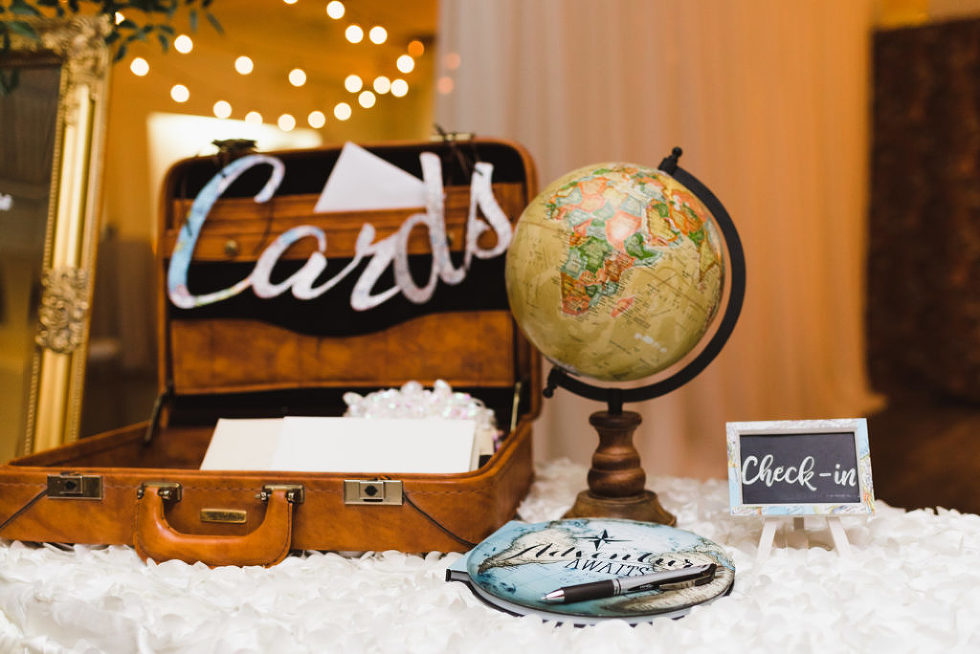 white table with brown suitcase on top for cards with a globe next to it and a check in sign for the wedding at the Canadian Canoe Museum Peterborough
