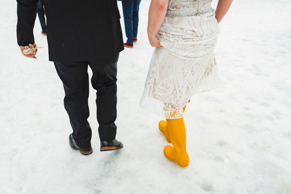 bride and groom walking in the snow, bride wearing bright yellow rain boots Canadian Canoe Museum wedding
