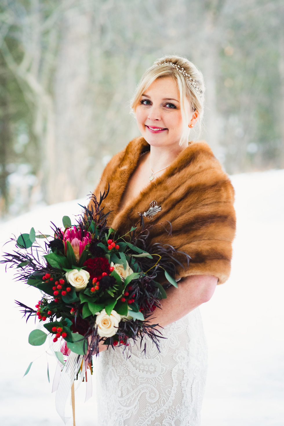 bride in wedding dress and fur draped over shoulders holding bouquet Canadian Canoe Museum wedding