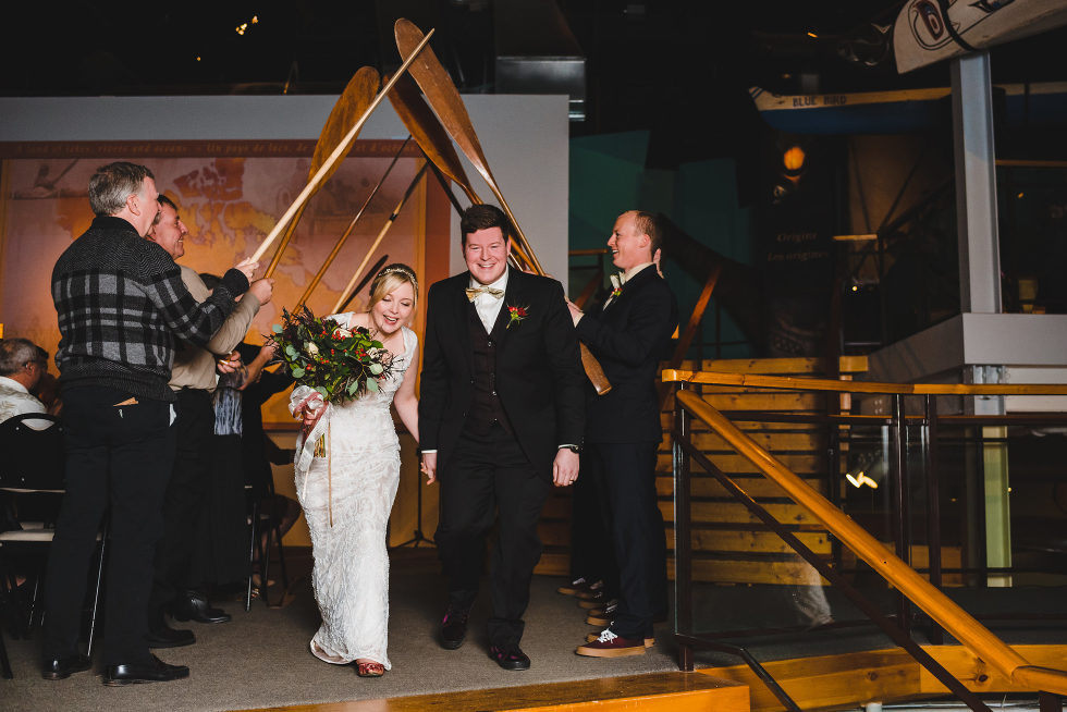 married couple walking under line of paddles being held above their heads How do I make my DIY wedding look amazing?