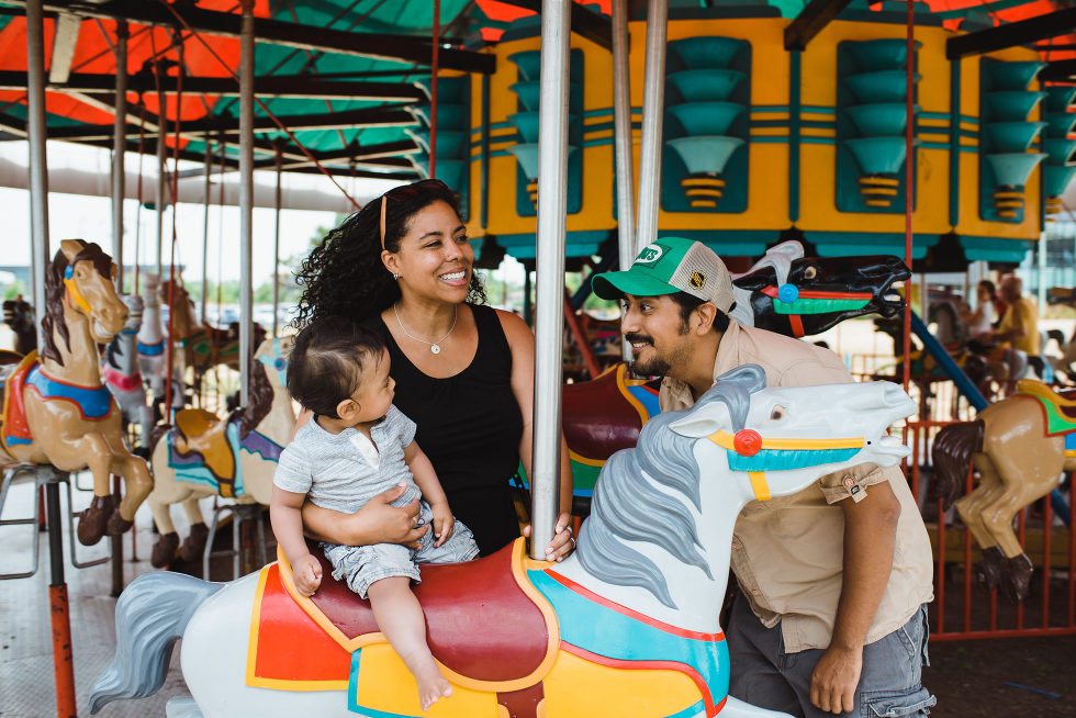 Mom and dad stand next to their baby riding a merry go round horse family photo session