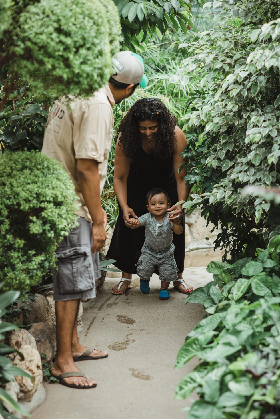 father watches as mother helps child walk through green gardens family photo sessions Gillian Foster