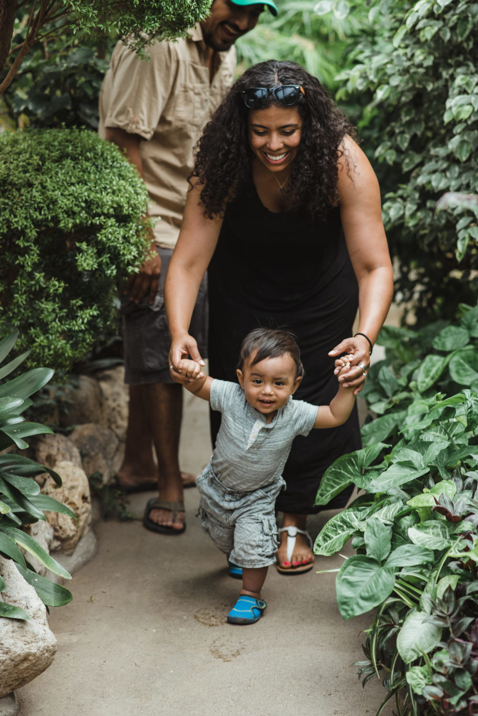mother helps young child walk through green gardens family photo sessions