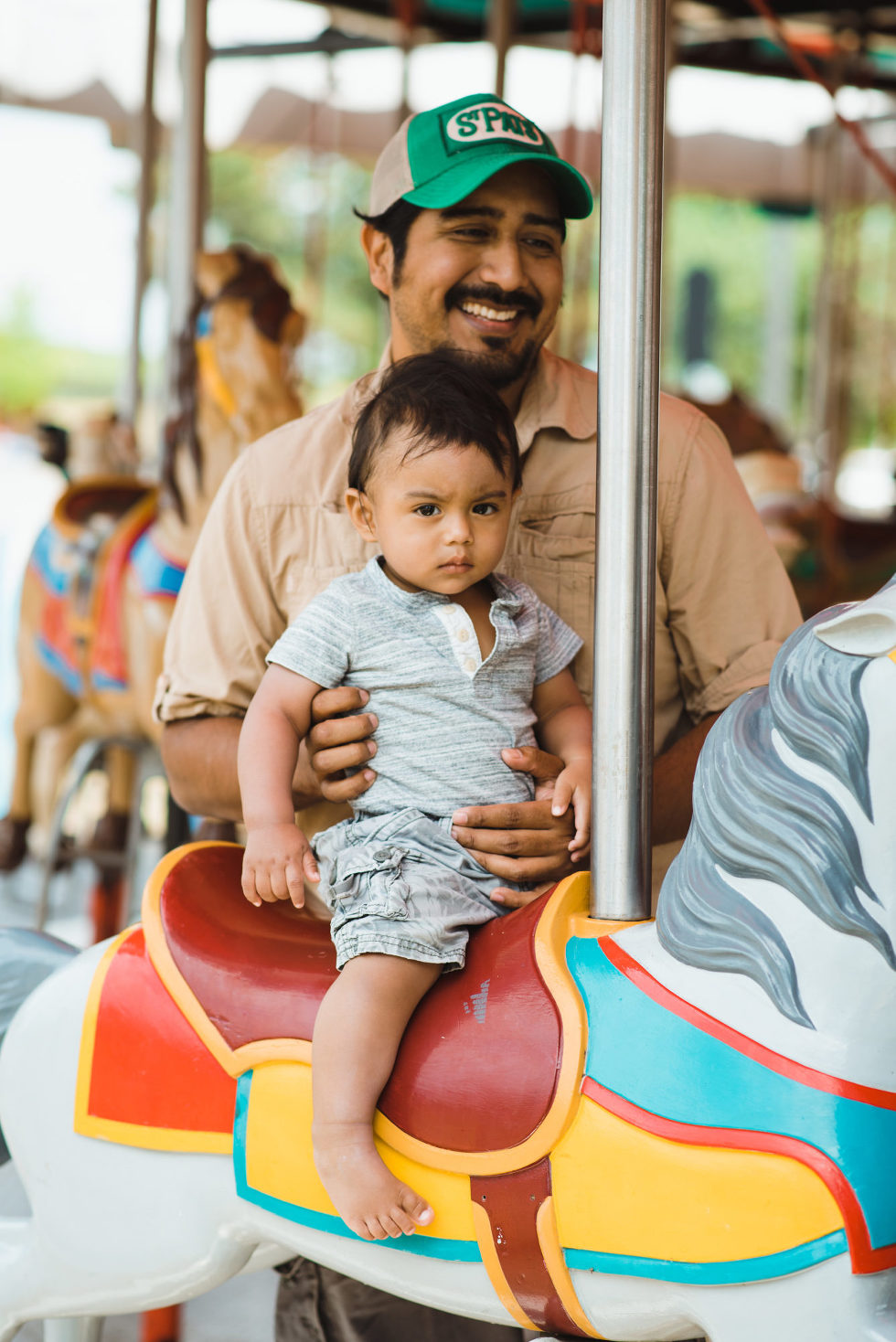 smiling dad holding his son on merry go round horse family photo session