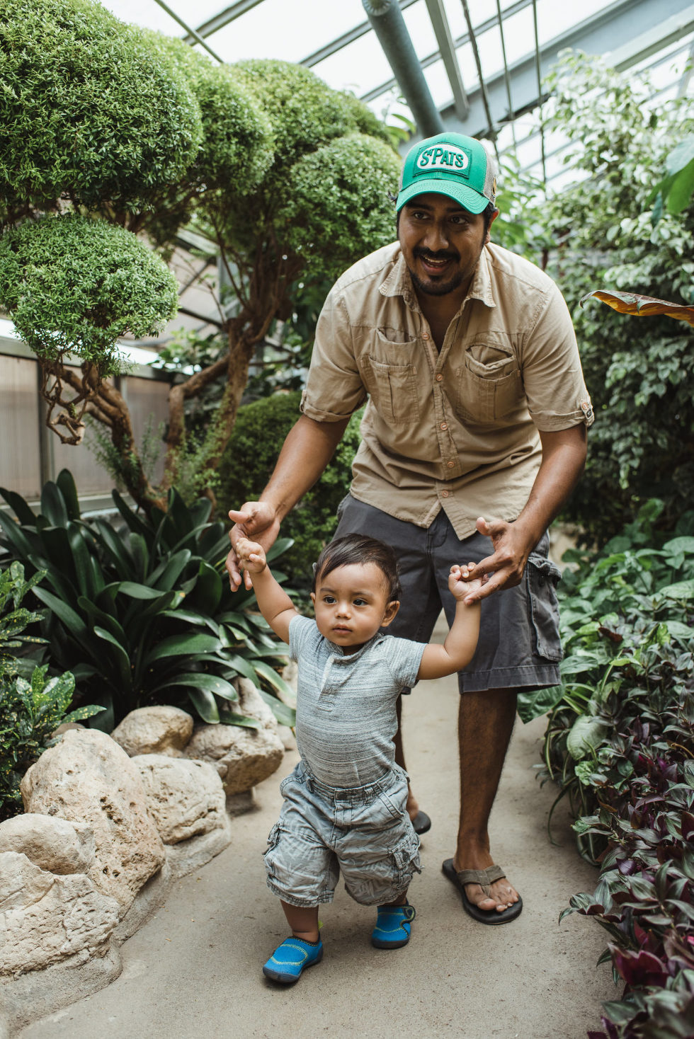 father helps young child walk through green gardens family photo sessions