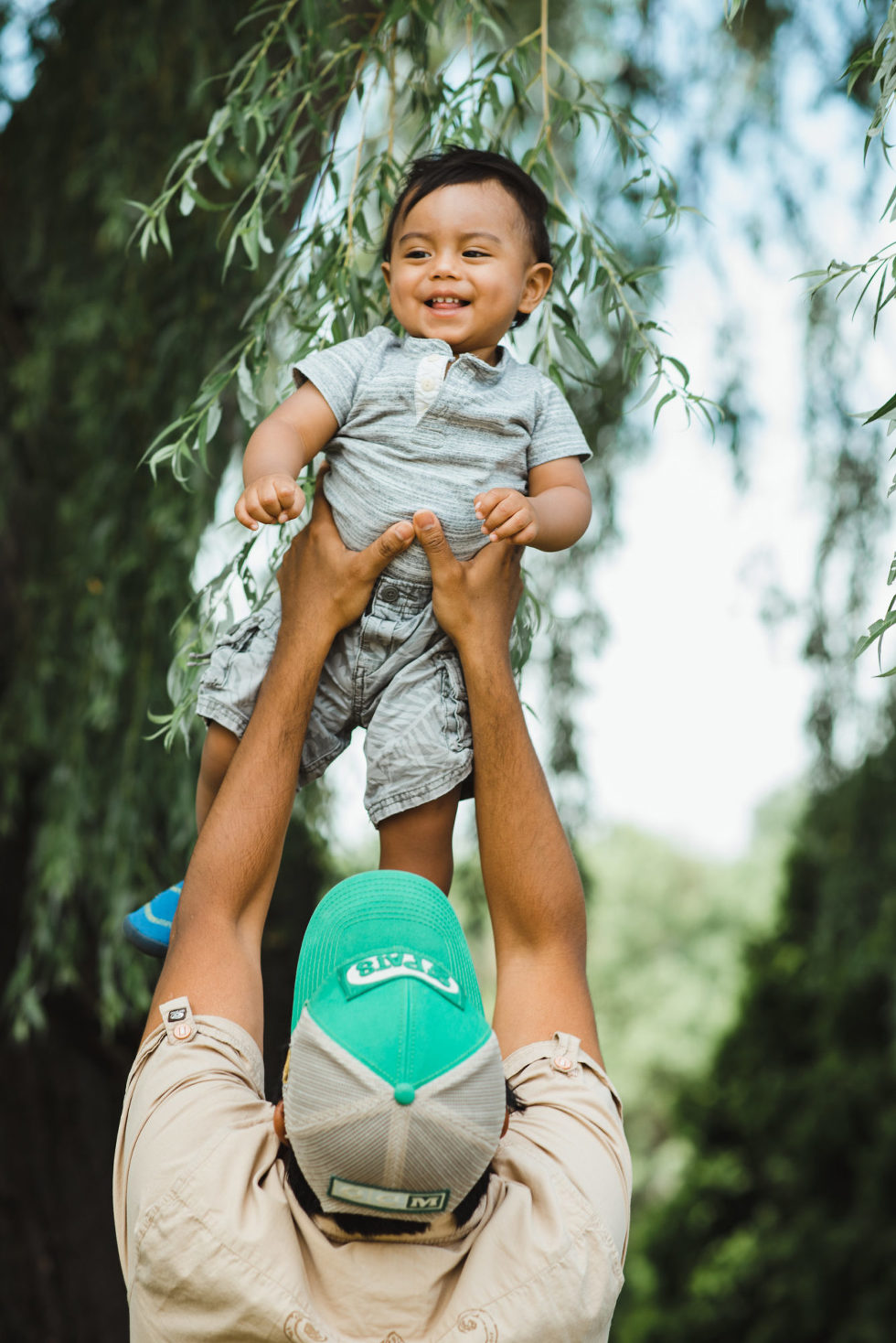 father holding his young smiling toddler in the air family photo session Gillian Foster
