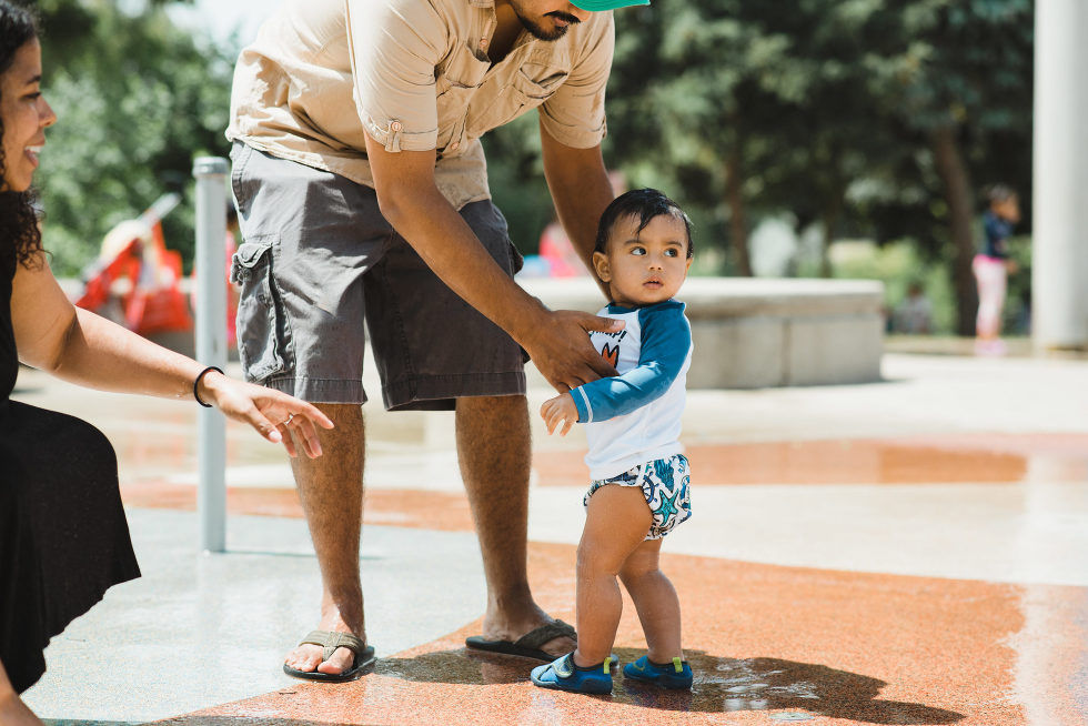 father and mother helping son walk through the water into splash pad at the park