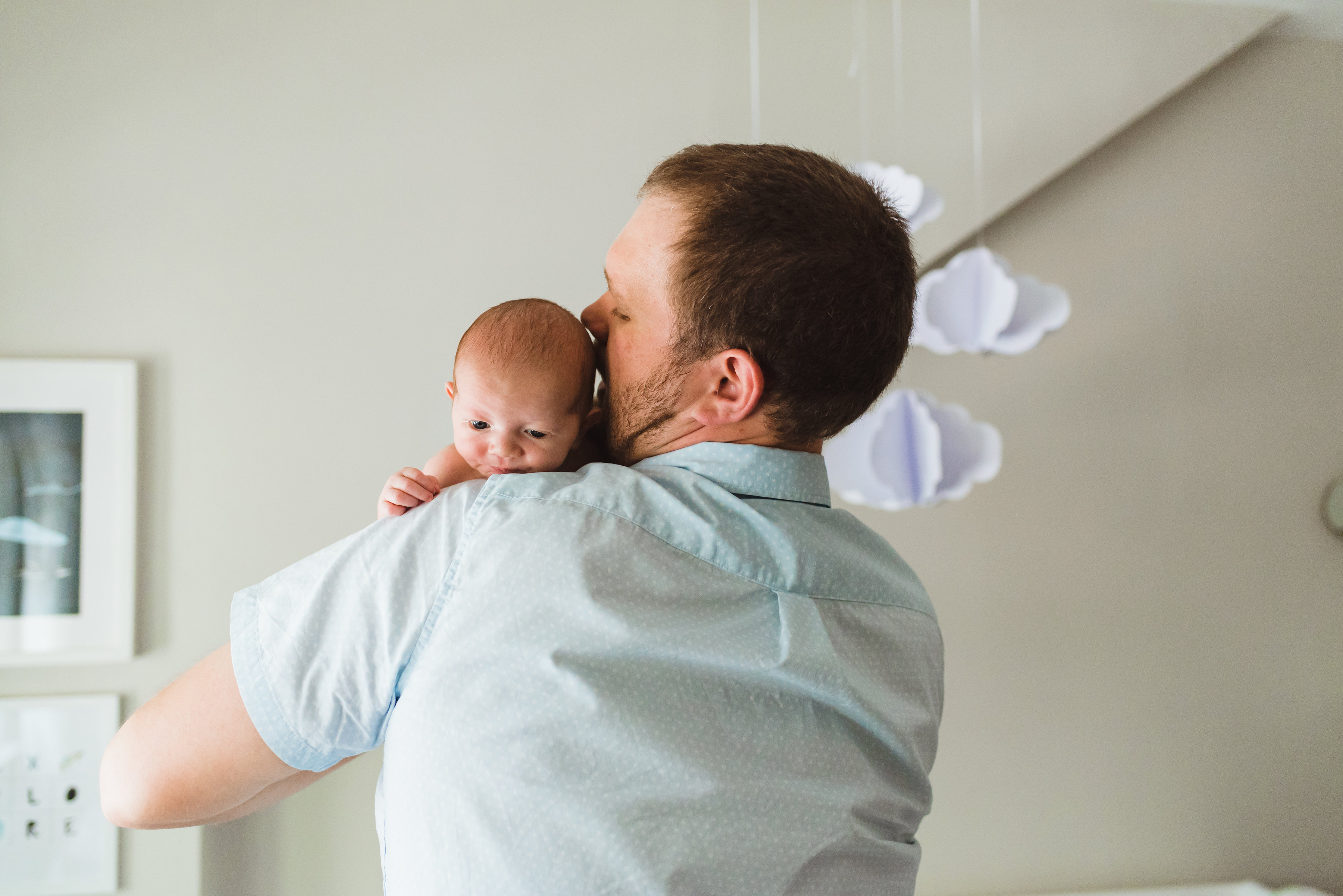 father holds newborn baby up to his shoulder Toronto family photography