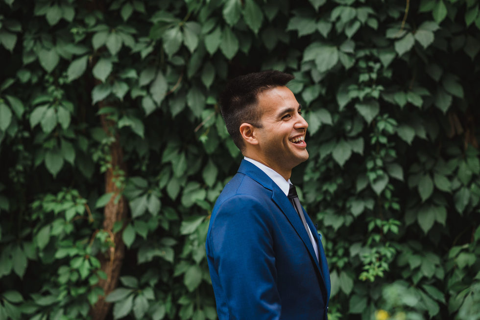 groom in blue suit smiling as he awaits his bride Toronto wedding photography