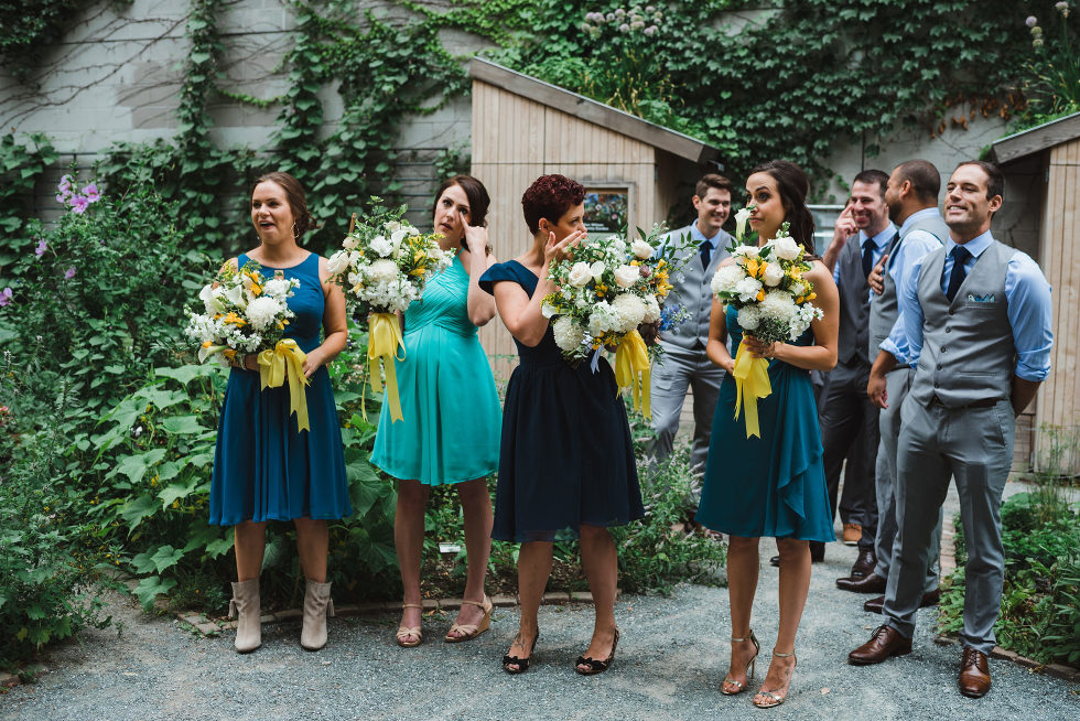wedding party in a garden reacting with tears as bride and groom share their first look in front of them Toronto Junction Craft Brewing wedding photography