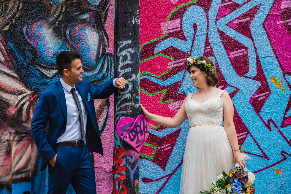 bride and groom leaning against a pole in Graffiti Alley in Toronto Junction Craft Brewing wedding photography