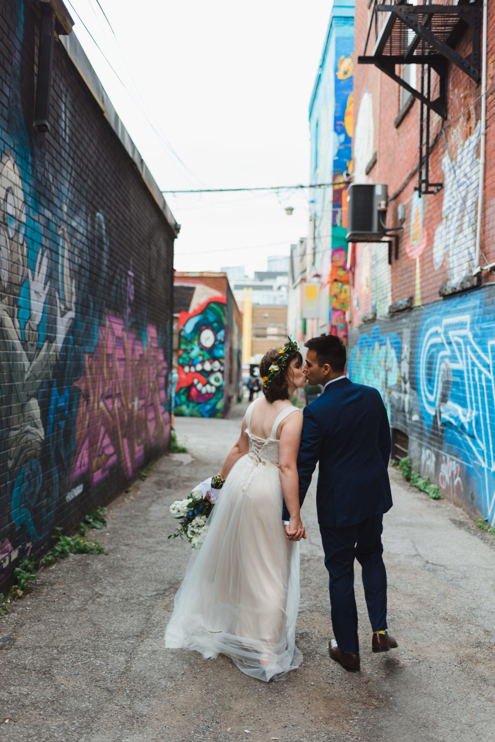bride and groom strolling through Graffiti Alley in Toronto as they kiss Junction Craft Brewing