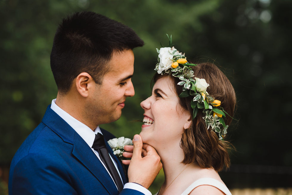groom places his hand on his brides chin as she smile back at him Toronto brewery wedding photography Gillian Foster