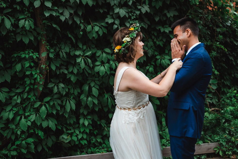 groom placing his hands over his smiling face reacts to first sight of his bride in her dress Toronto brewery wedding photography