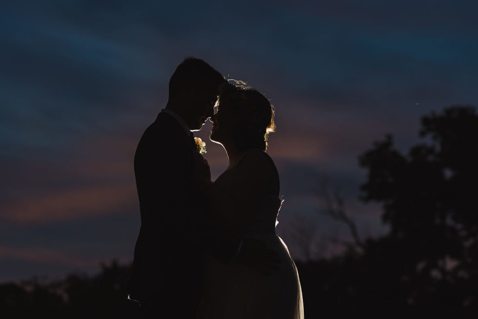 silhouette of a bride and groom holding each other at dusk Junction Craft Brewing Toronto wedding photographer Gillian Foster