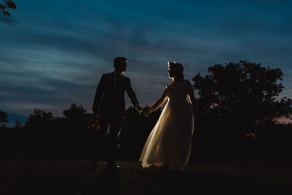 silhouette of a bride and groom holding hands at dusk Junction Craft Brewing Toronto wedding photographer Gillian Foster