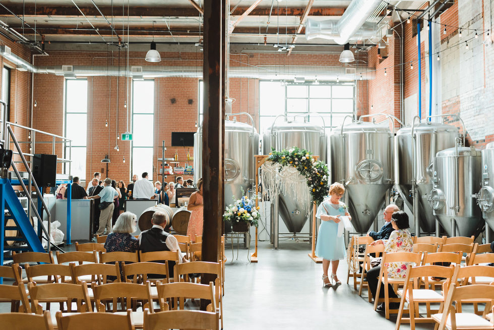 wedding ceremony set up in front of brewing tanks Toronto Junction Craft Brewing wedding