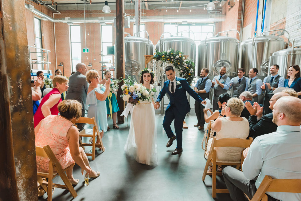 bride and groom dancing their way down the aisle as they exit the ceremony Toronto Junction Craft Brewing