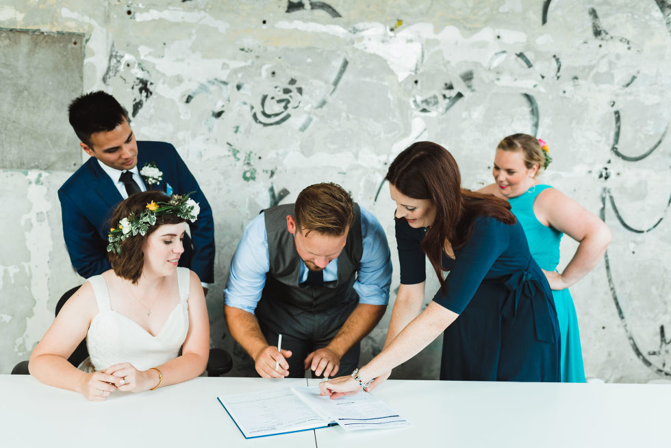 bride and groom watch as officiant shows groomsman where to sign wedding certificate Toronto Junction Craft Brewing