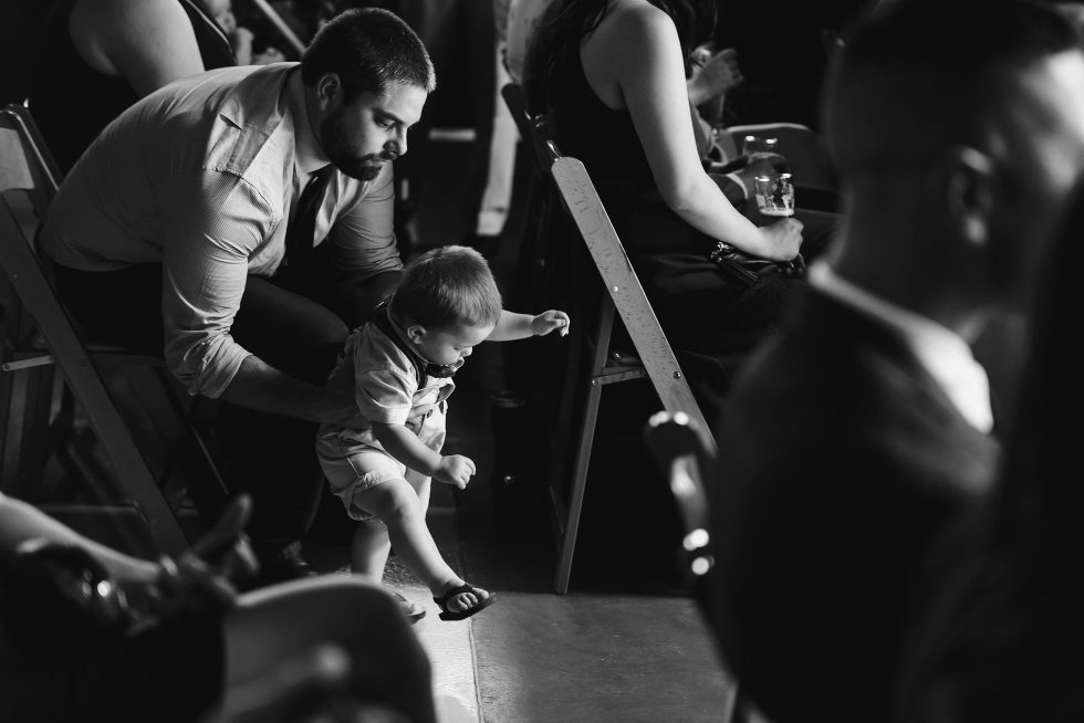 father holding his toddler up in the aisle before the wedding ceremony Toronto Junction Craft Brewing